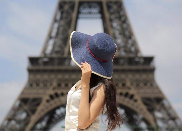 Una turista delante de la Torre Eiffel de París