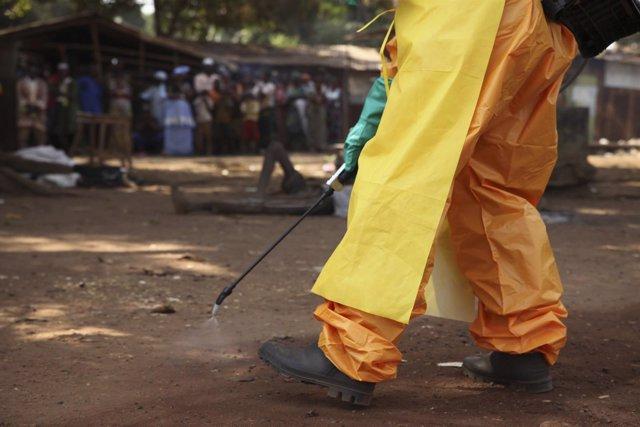 Un trabajador de Cruz Roja desinfecta en Guinea una zona afectada por ébola