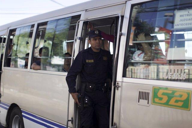 Un policía custodia un autobús en la capital de El Salvador
