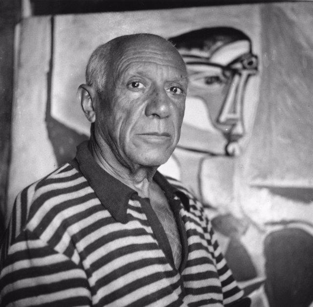 Pablo Picasso con un cuadro de fondo
