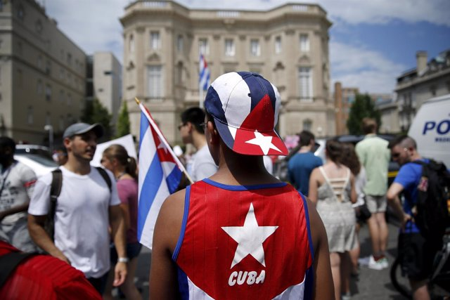 People gather outside the Cuban embassy after the Cuban flag was raised in a cer