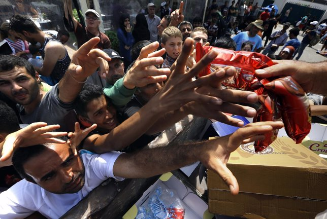 Refugiados sirios intentan alcanzar comida de ayuda humanitaria en Kos (Grecia)
