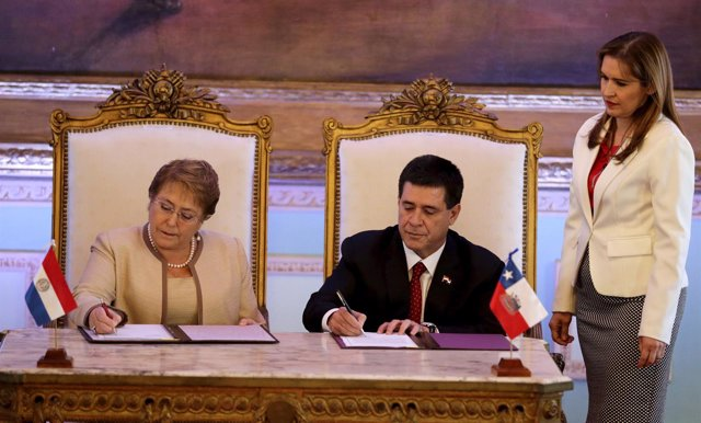 Paraguay's President Horacio Cartes and Chile's President Michelle Bachelet sign