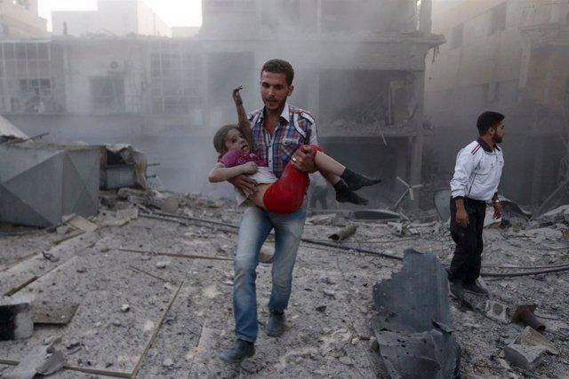 Un hombre con una niña en Siria trasun bombardeo en Damasco