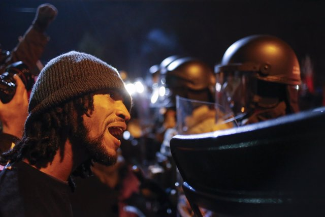 Un manifestante le grita a un policía en Ferguson.