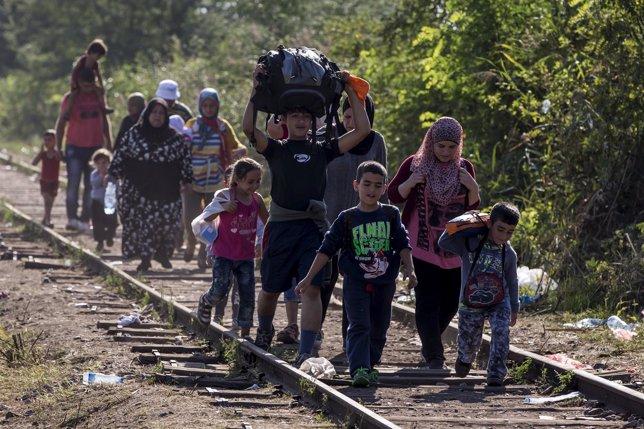 Refugiados andando por la via del tren
