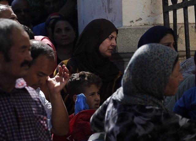 Inmigrantes esperan en una comisaría de Policía en la isla griega de Kos