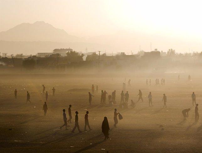Personas caminando en un campo de Kabul al amanecer