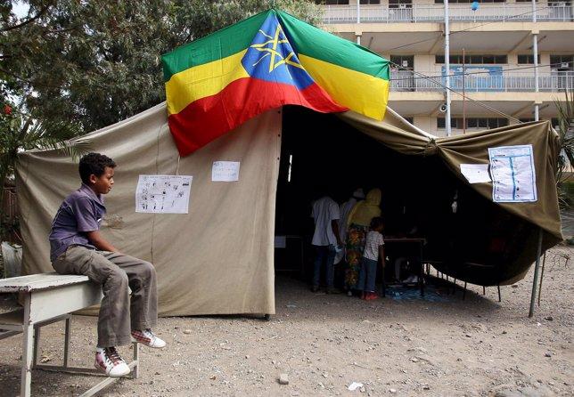 Un niño sentado junto a un colegio electoral en Addis Abeba (Etiopía)