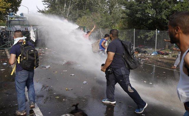 La Policía húngara llanza agua a los refuxaos.