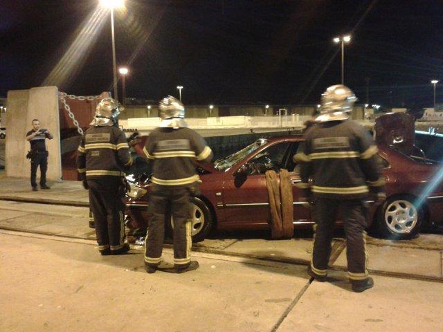 Bomberos rescatan el vehículo caído al agua en el puerto