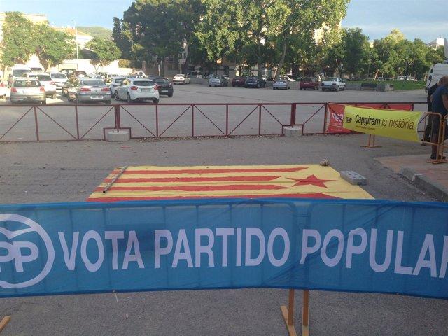 Pancarta del PP junto a una estelada ante el mismo lugar de un mitin de PP y CUP