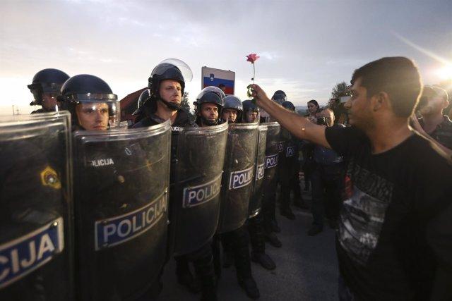 Refugiado sostiene una rosa ante la Policía eslovena, en la frontera con Croacia