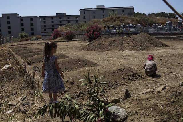 Dos niños refugiados sirios juegan junto a la tumba de su abuela en Catania