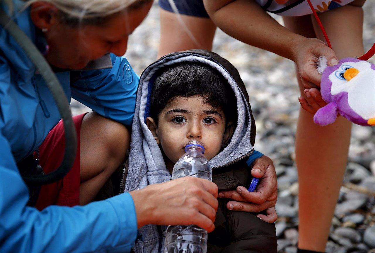 Voluntarias dan agua y un juguete a un niño refugiado sirio en Lesbos