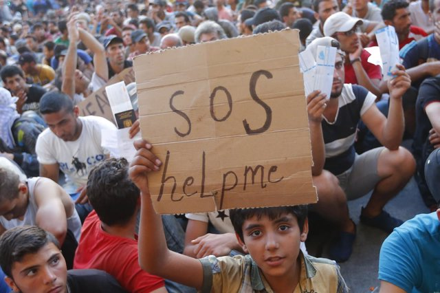 Un menor refugiado con una mensaje de 'SOS' en Budapest