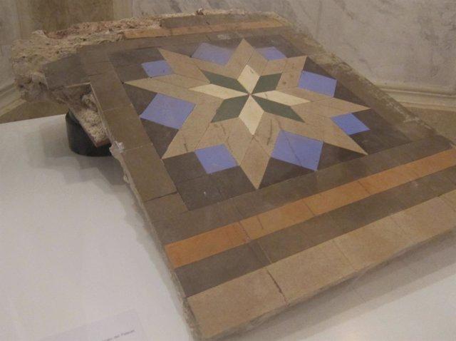Una pieza del mosaico Nolla procedente del Palauet junto a la fábrica