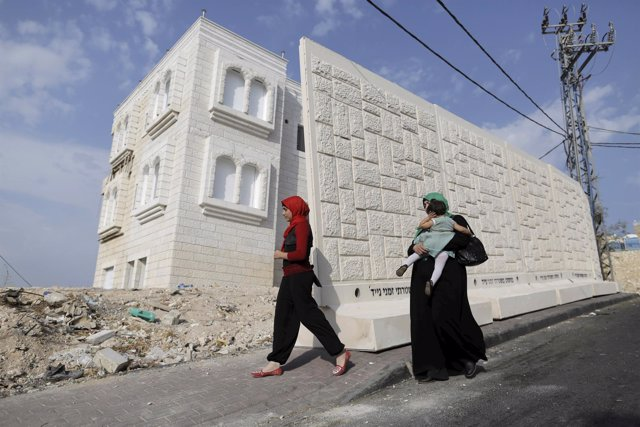 Women walk past a newly erected temporary concrete wall that measures around 10