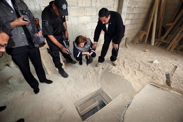 Mexico's Attorney General Gomez Gonzalez looks into the entrance of a tunnel con