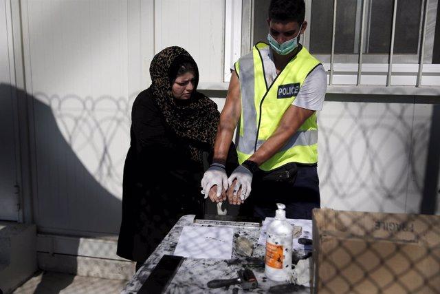 Un hombre toma las huellas a una refugiada afgana en el centro de Moria