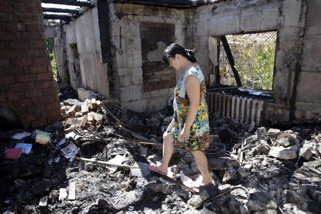 Una mujer camina entre los escombros de una casa en Donetsk (Ucrania)