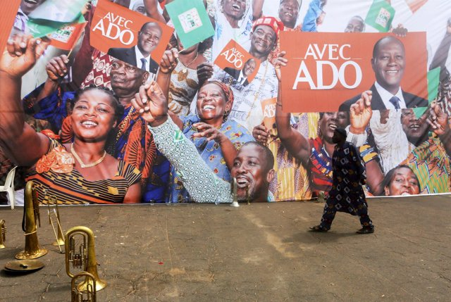 Un hombre camina delante de carteles de Alassane Ouattara