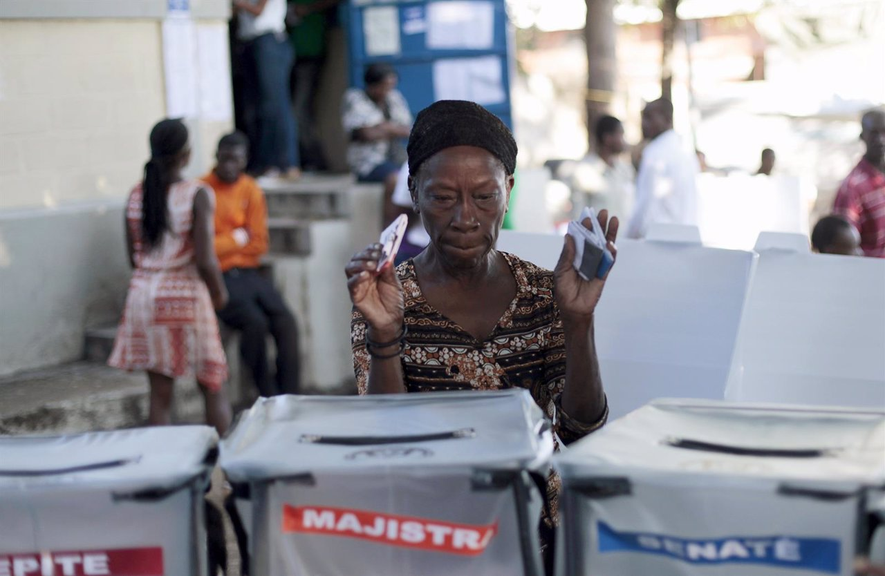 A woman asks where to deposit her ballots at a polling station in Port-au-Prince