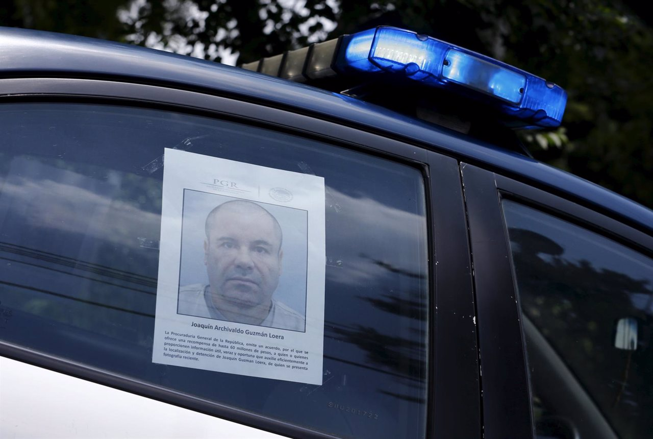 A police vehicle is seen a poster with a photo of drug lord Joaquin