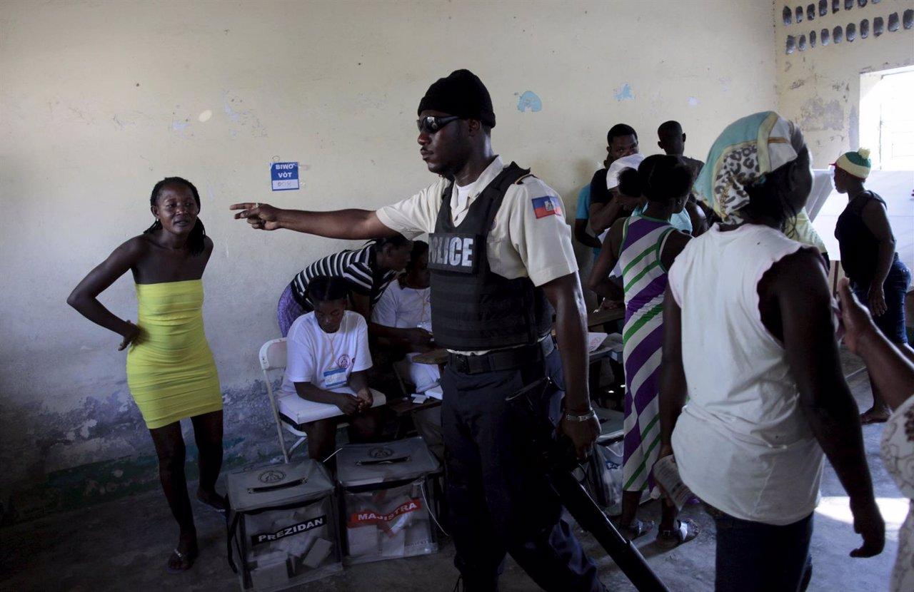 Policía Nacional dice a una mujer que dejen que las urnas en Haití