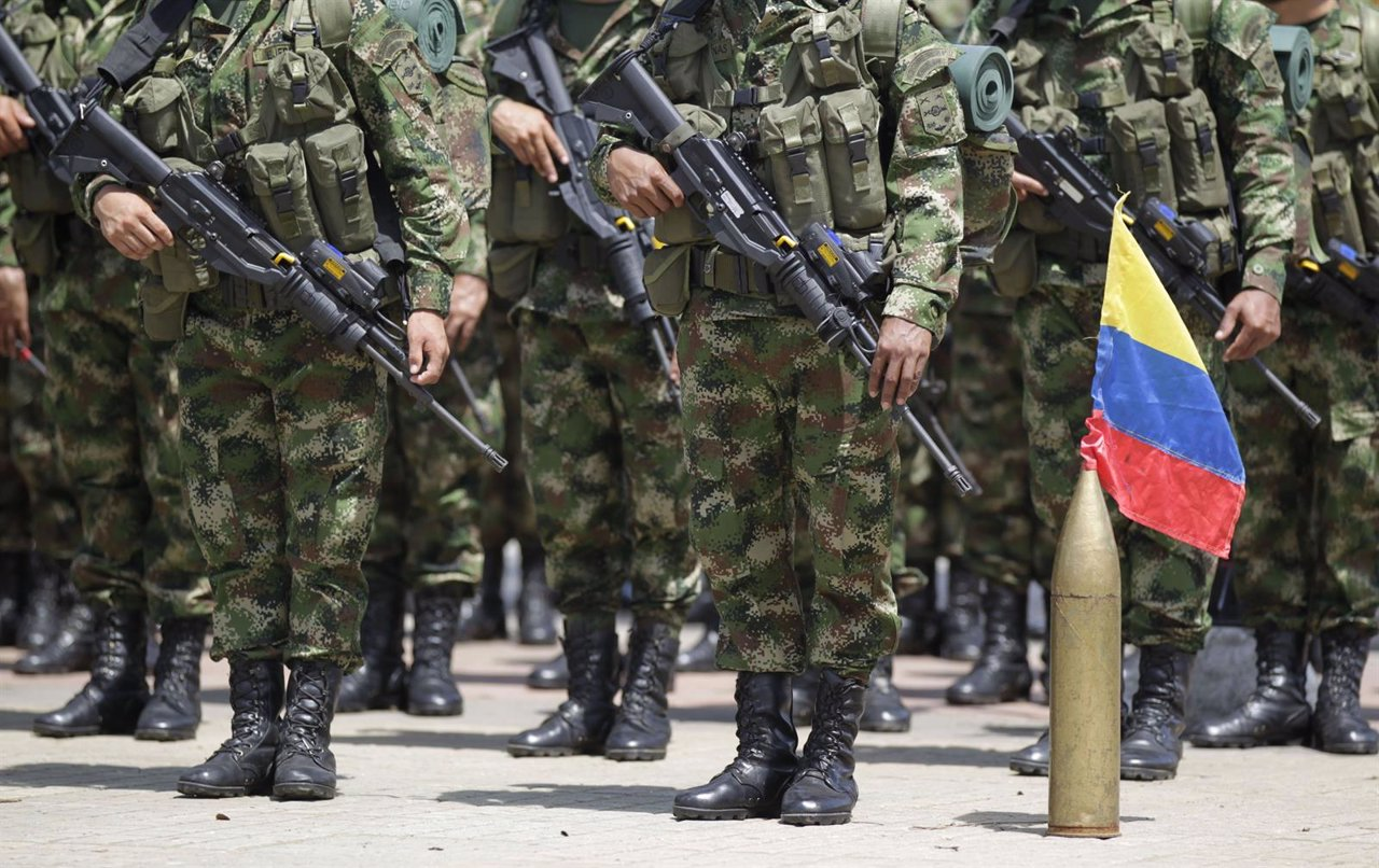 Colombian soldiers stand at attention next to their national flag during an inau