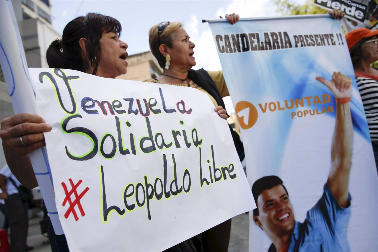 Supporters of jailed opposition leader Leopoldo Lopez hold placards and a pictur