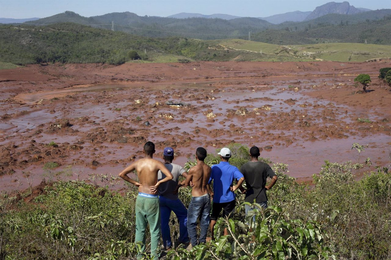Residents observe the Bento Rodrigues district covered with mud after a dam owne