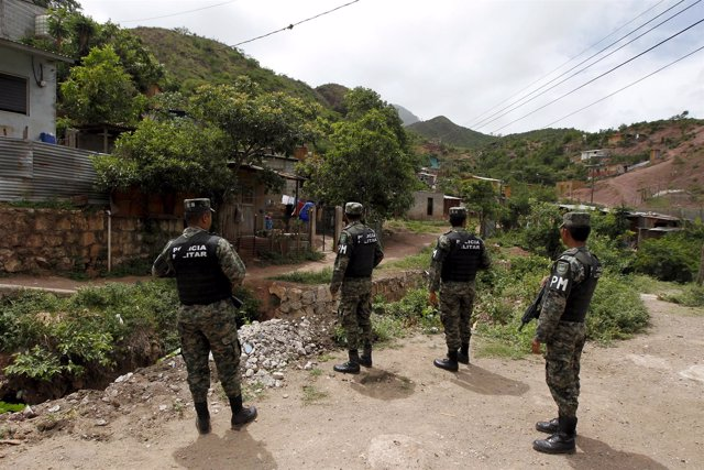 Members of the Military Police for Public Order (PMOP) patrol an impoverished ne