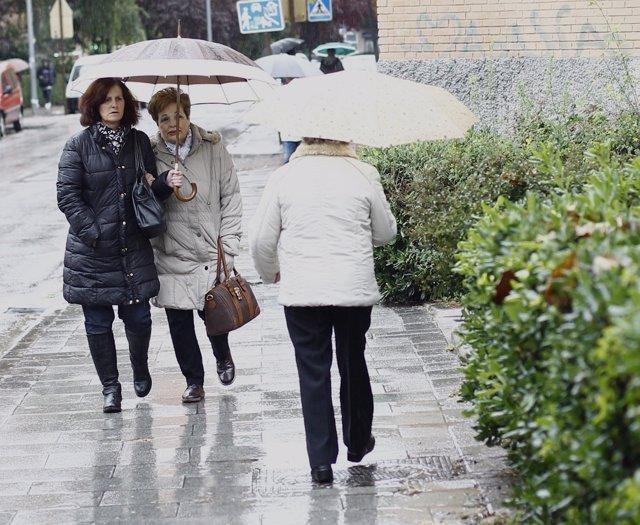 Gente bajos sus paraguas pasean por la calle.