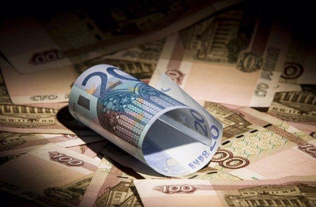 Monedas de euros encima de otros billetes
