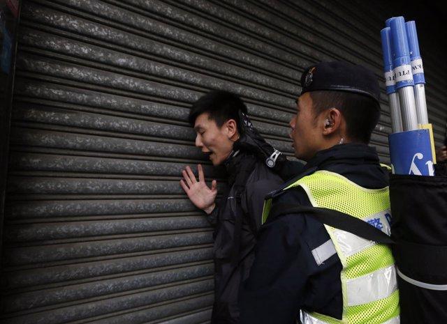 Un policía chino detiene a una persona