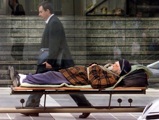 Un hombre de negocios camina mientras un indigente, pobre, descansa en un banco