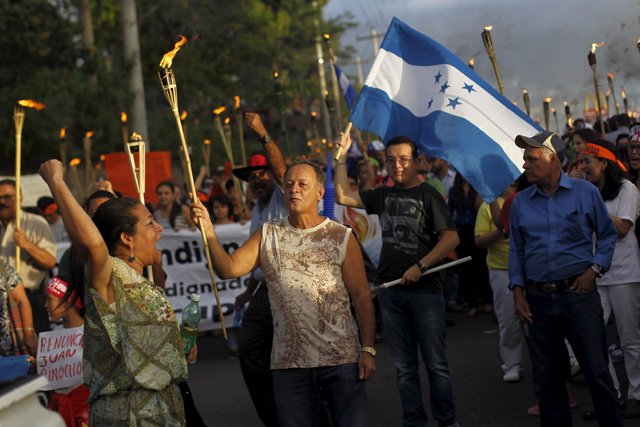 People take part in a march to demand the resignation of Honduras' President Jua