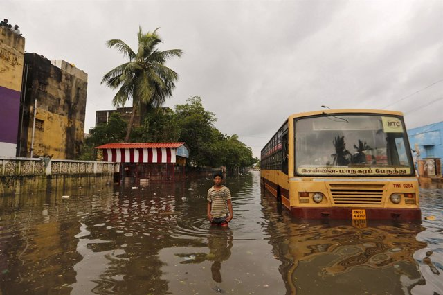 A boy wades next to a partially submerged bus in a flooded locality in Chennai