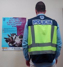 Un agente ante el cartel de la campaña contra la trata de mujeres