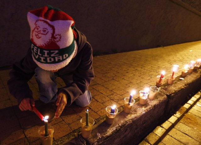 A boy lights candles during Little Candles' Day in Bogota