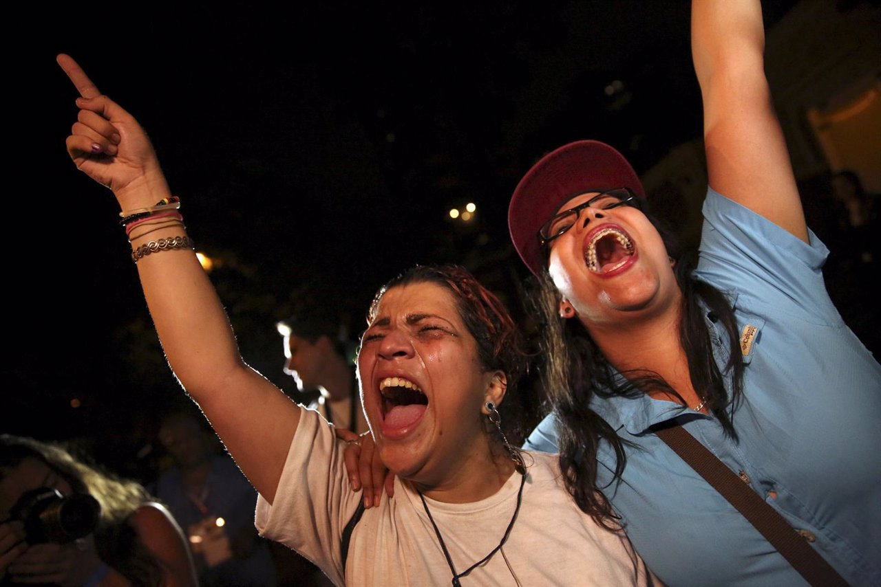 Opposition supporters shout while they celebrate their victory on a street in Ca