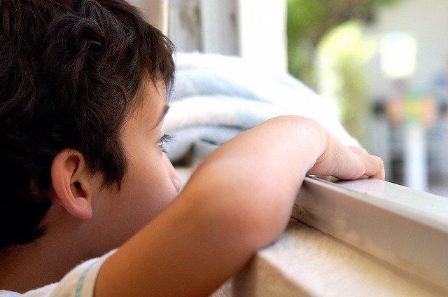 Autismo, niño mirando por la ventana.