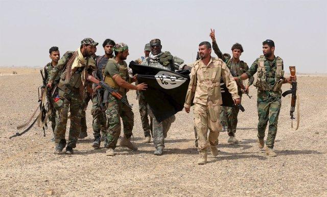 Militantes del Estado Islámico portan una bandera del Estado Islámico