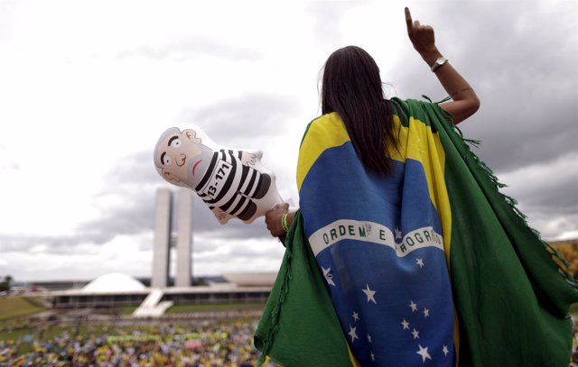 A demonstrator gestures as she holds an inflatable doll of Brazil's former presi