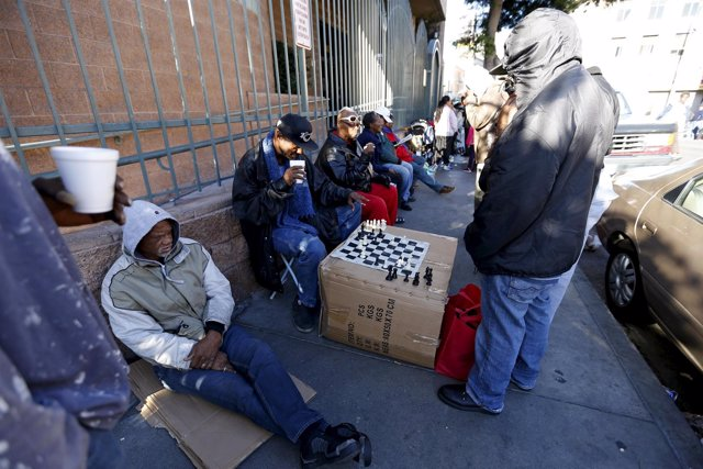 Two people play a game of chess as they wait in line for an early Thanksgiving m