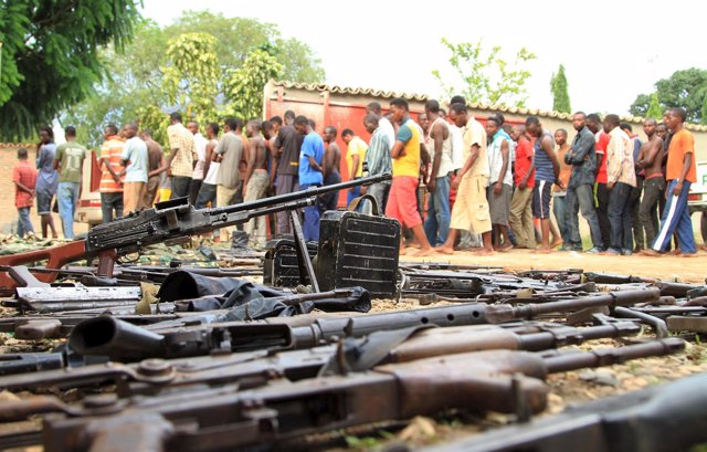 Suspected fighters are paraded before the media by Burundian police near a recov