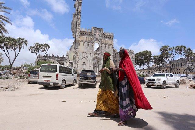 Mujeres somalíes caminan delante de restos de catedral de Mogadiscio