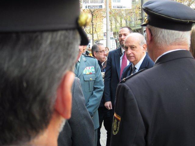 El ministro del Interior, Jorge Fernández Díaz, ante dos policías nacionales