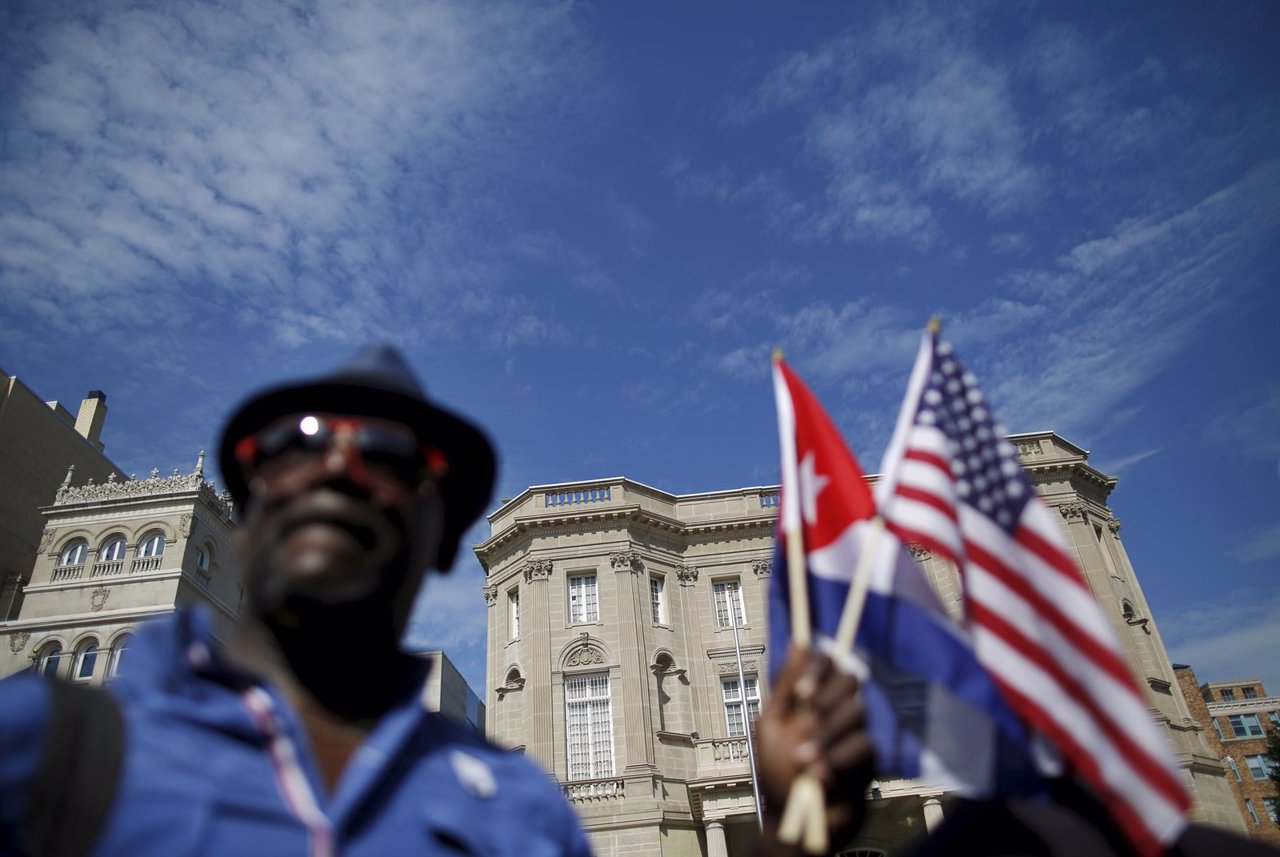 Newly reopened Cuban embassy is seen in the background as a man holds U.S. And C